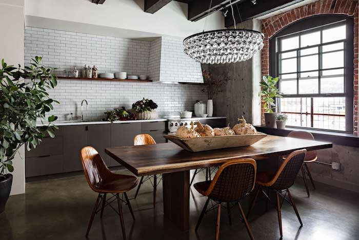 comment aménager une petite cuisine industrielle, crédence en carrelage blanc, meuble cuisine gris anthracite, table et chaises en bois, revetement sol effet beton