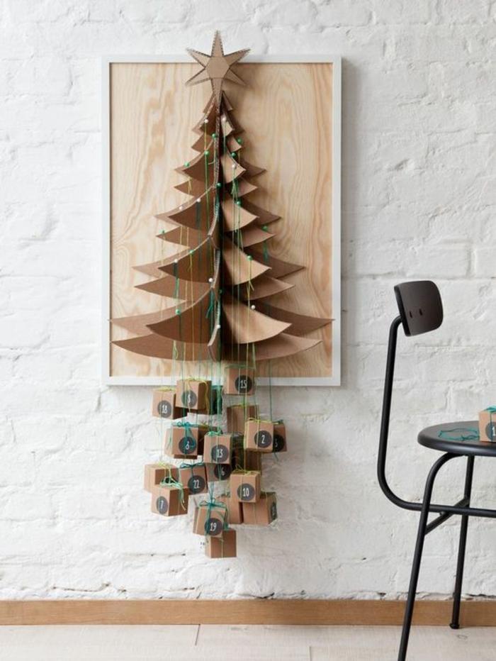 arbre de Noel en carton sur un tableau de bois, cadeaux suspendues, mur en briques blanches