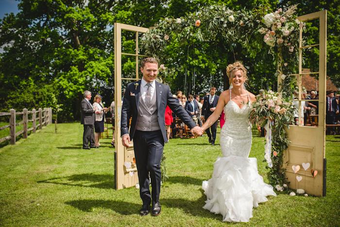 arche fleurie de mariage, champetre, portes en bois vintage avec décoration de guirlandes fleuries, couple mairée