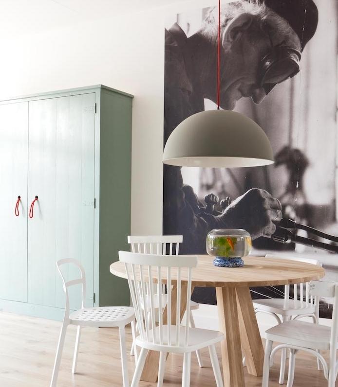 armoire vert gris dans une salle à manger scandinave avec table ronde et chaises blanches en bois et metal, panneau décoratif noir et blanc, parquet clair