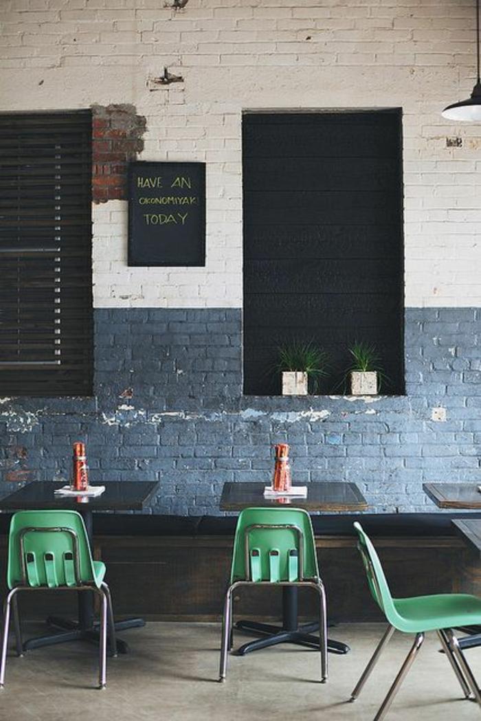 couleur bleu gris dans un bistro en Grèce sur un mur en briques colorées moitié en bleu moitié en blanc