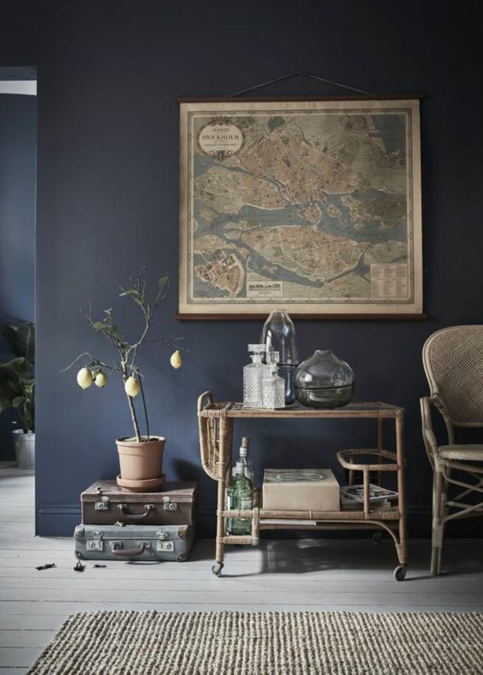 couleur bleu saphir au mur d'une entrée en style voyageur avec une grande carte du monde ancienne