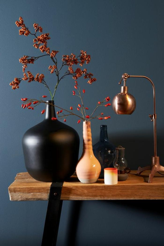 couleur bleu gris dans l'' entrée d'un appartement avec table en bois rude et pieds en métal noir avec vase en céramique noire