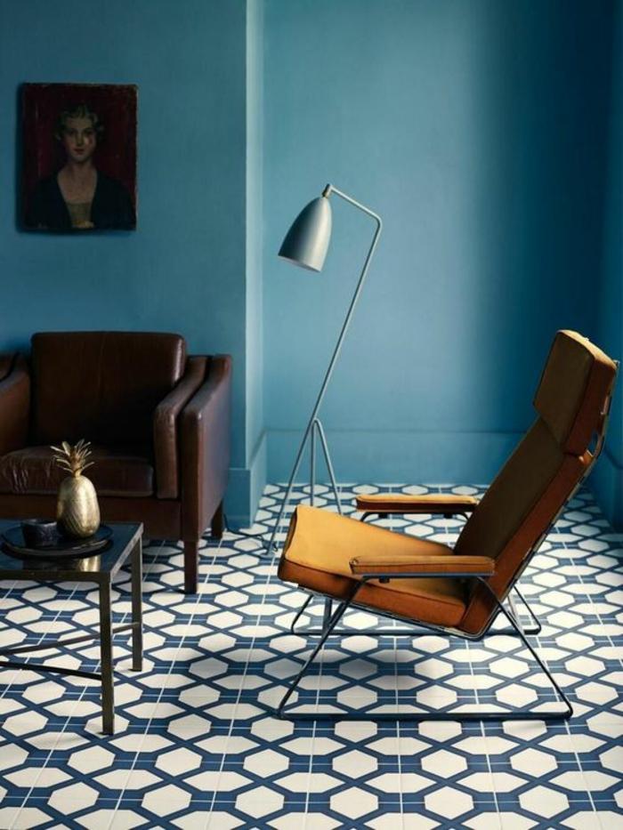 deco salon bleu canard avec fauteuil et chaise moderne inclinée en arrière luminaire posé au sol avec abat-jour métallique
