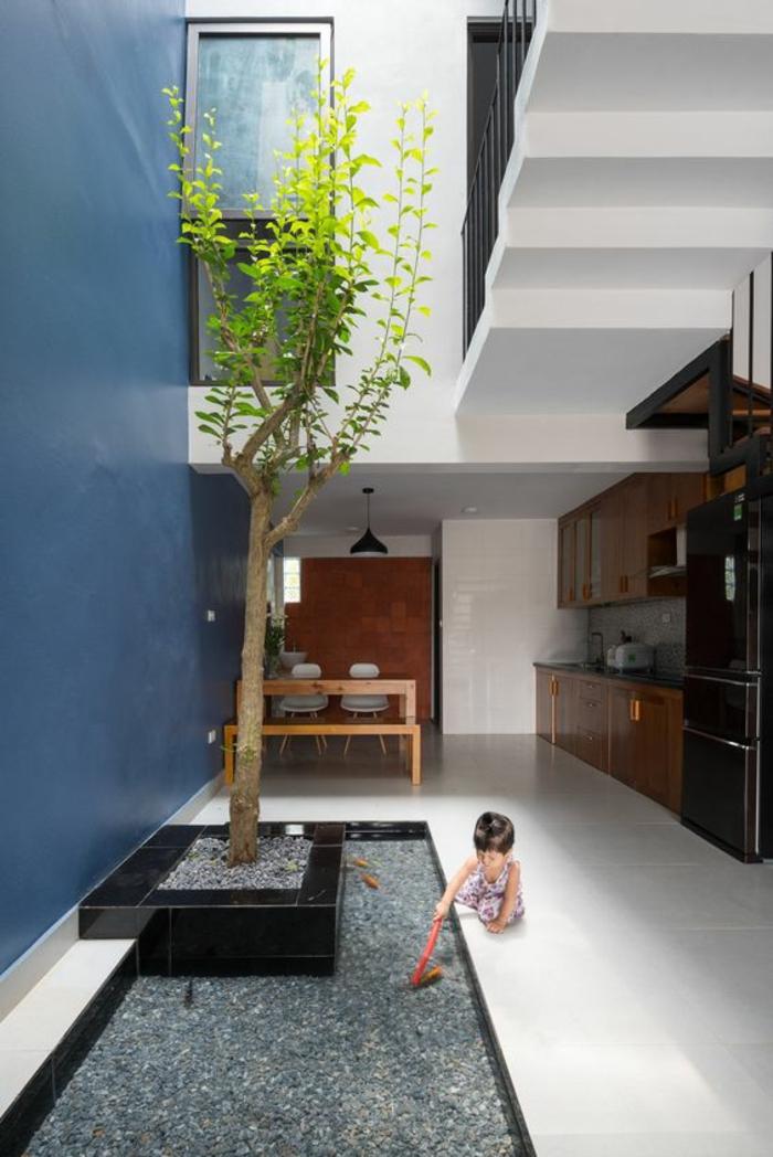 deco salon bleu canard mur en bleu gris pièce a deux niveaux avec escalier blanc grand espace et un arbre dans le coin pour les jeux des petits