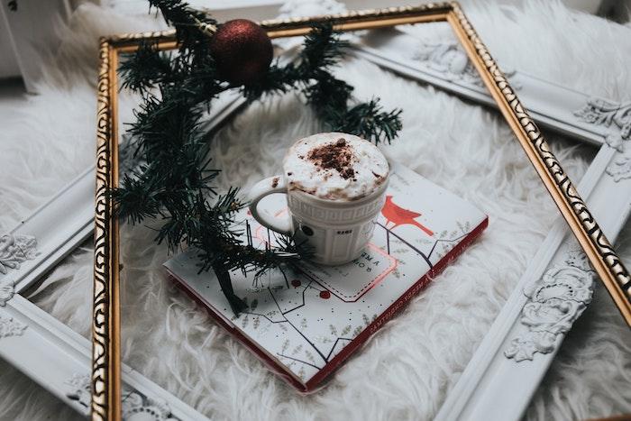 chocolat chaud avec boisson avec beaucoup de crème fraîche, cadre doré, livre, branche de pin et boule de noel rouge, fond ecran noel