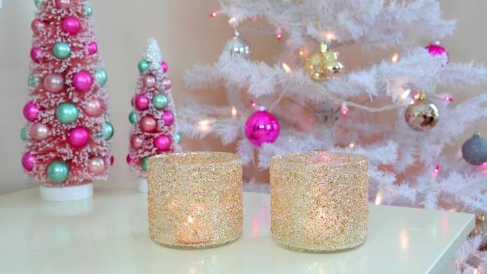 activite de noel, bougeoirs en verre pailletés, paillettes couelur or, bougies dedans, sapin de noel blanc sur le fond, decoration boules de noel bleus et rose