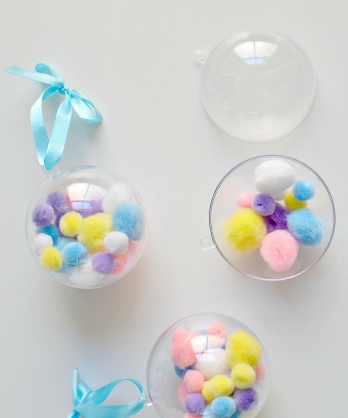 boule de noel transparente, bricolage facile, deco sapin de noel en pompons colorés en bleu, rose, jaune et violet, ruban bleu pour suspendre