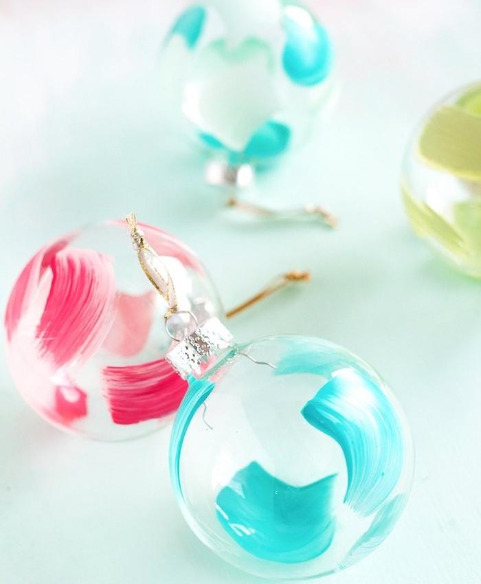 decoration de noel a faire soi meme, boule de noel en plastique, décorée de touches de peinture rouge et bleue, décoration sapin de noel facile