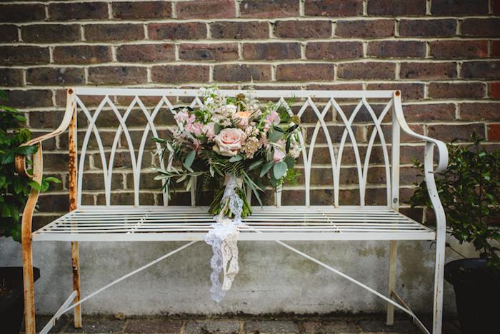 bouquet champetre de mariée, décorée de dentelle blanche sur un banc metallique rouillé, mur de fond en briques