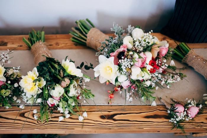 bouquet champetre de fleurs. tiges enveloppés de jute, sur un chemin de table en bande de jute