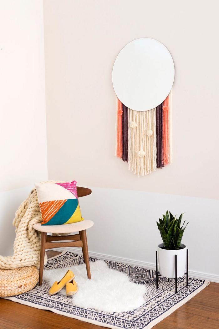 bricolage avec de la laine pour donner un accent bohème chic à son intérieur, déco originale avec une tenture murale à pompons et un miroir rond