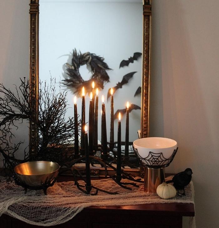 accessoire halloween, meuble en bois avec miroir vintage décorés en tissu blanc et bougeoirs noirs