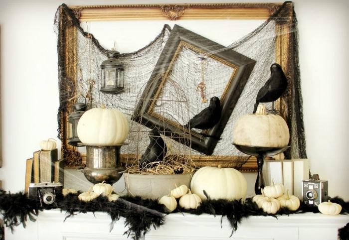 deco halloween, intérieur aux murs blancs et cadres noires avec toile d'araignée pour Halloween et petites citrouilles blanches