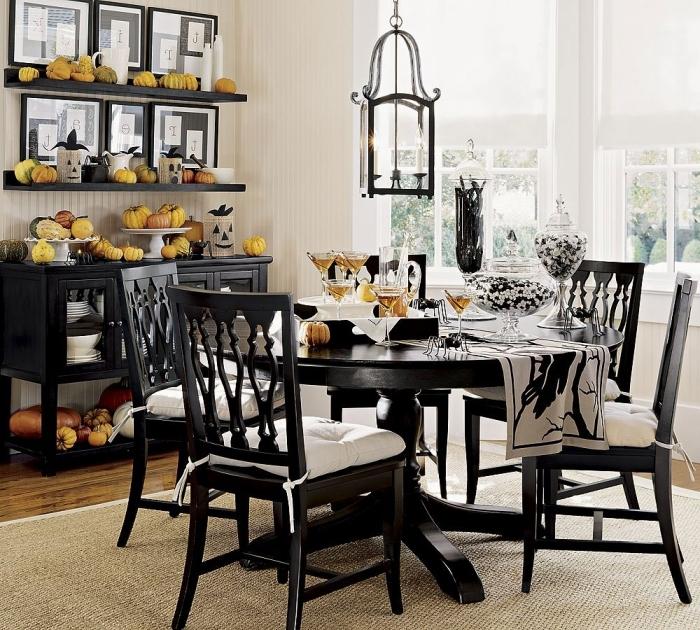 apero halloween, idée comment aménager la salle à manger en blanc et noir, table ronde noire avec chaises noires et housses blanches