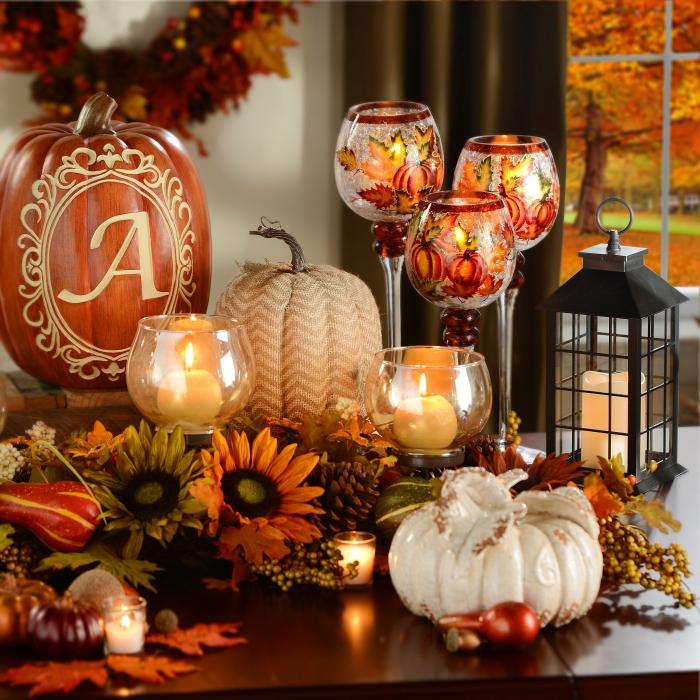activité manuelle halloween, bougies blanches dans récipients ovales en verre, feuilles et fleurs séchées orange et vert