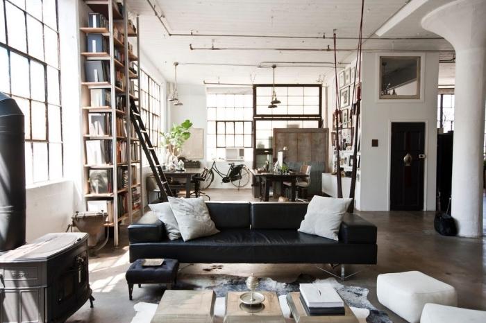 lampe industrielle, salon aux murs blancs et plancher marron, meubles de salon avec canapé en cuir noir et tabourets en cuir blanc