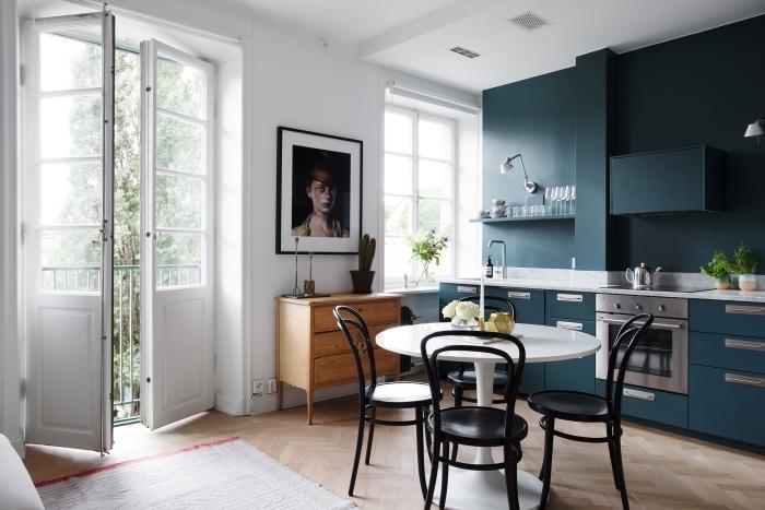 deco nordique, cuisine avec meubles en bleu foncé et étagères murales, table à manger blanche avec chaises noires