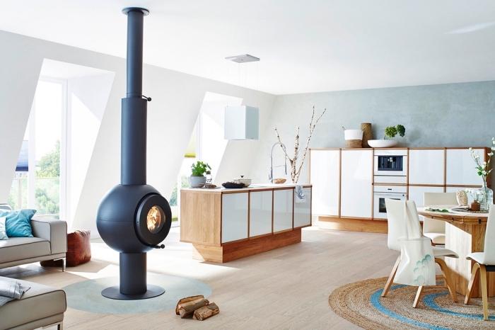 inspiration scandinave, meubles de cuisine blancs en bois, revêtement de sol en bois stratifié, cheminée noire ronde moderne