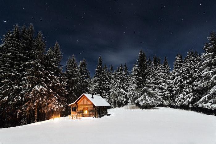 paysage hiver fond ecran, montagne enneigée, petite cabane avec lumière à l intérieur, arbres, sapins couverts de neige