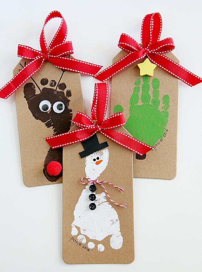 carte de noel maternelle empreintes de main et de pieds sur carton, motif sapin de noel, bonhomme de neige et déco de ruban rouge