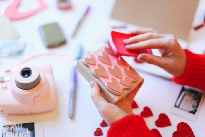 technique scrapbooking pour faire petits coeurs glitter, appareil photo rose et crayons différentes couleurs