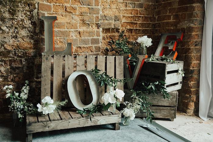 idée de caisses en bois déco et palettes bois rustiques, lettres capitales amour, guirlandes vertes et fleurs blanches, mariage champetre chic