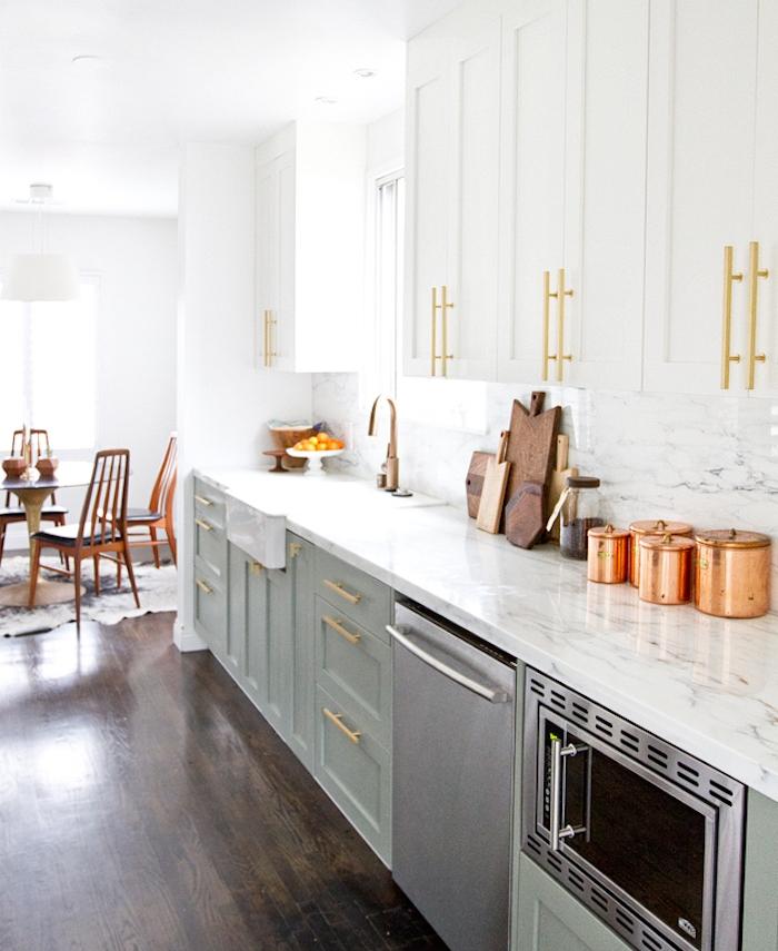 cuisine campagne chic avec meuble bas cuisine vert celadon et meuble haut blanc et poignées de porte dorées, parquet marron, électroménager inox, deco en bois et cuivre