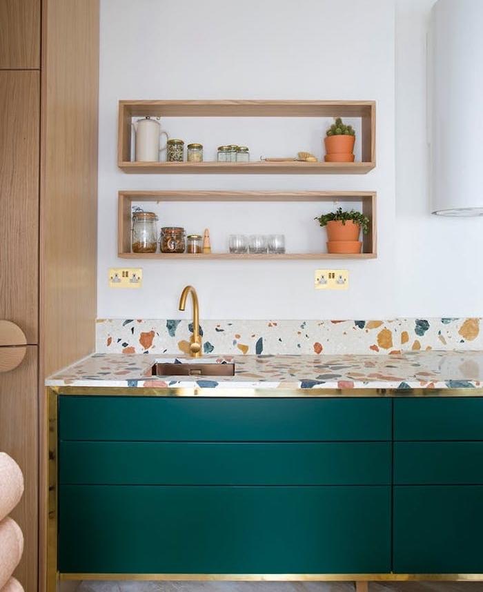 modele de cuisine ancienne avec meuble couleur vert émeraude, plan de travail à taches colorées, robinetterie dorée, étagères en bois ouvertes