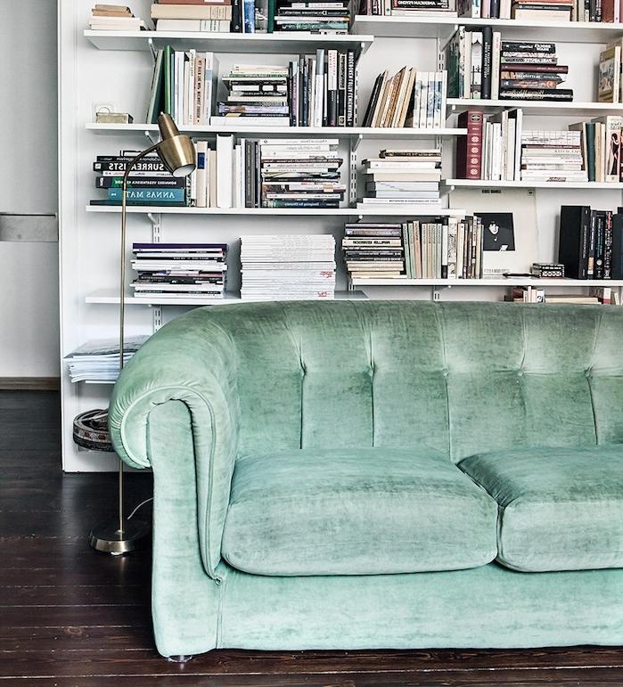 canapé couleur vert céladon dans un salon scandinave avec bibliotheque blanche à plusieurs rayons sur le fond et parquet marron