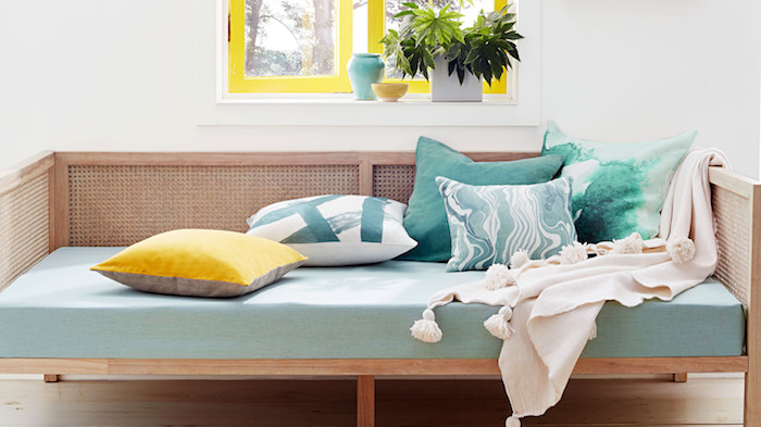canapé en bois avec matelas couleur céladon, décoré de coussins, bleu, vert et jaune, couverture gris clair, fenêtres avec cadres jaunes, mur de fond blanc