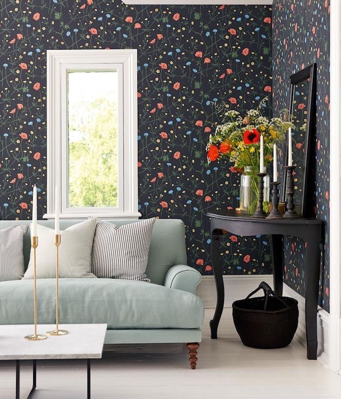 canapé vert céladon sur un mur de fond à papier peint noir floral à petites fleurs bleues et rouges, table d appoint décoraive noire, table basse en plateau de marbre et pieds de métal noirs