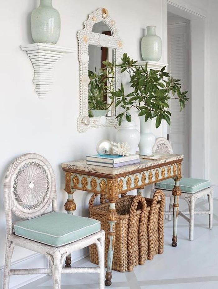 ceramique celadon, et coussins de chaises couleur vert céladon, panier tressé et une table entrée maison à déco dorée, plantes livres, miroir baroque, style colonial, bord de mer
