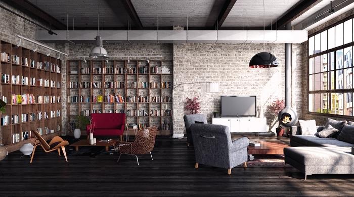 mobilier industriel, salon loft aux murs briques et plancher bois noir, meubles de salon avec canapé et fauteuils gris