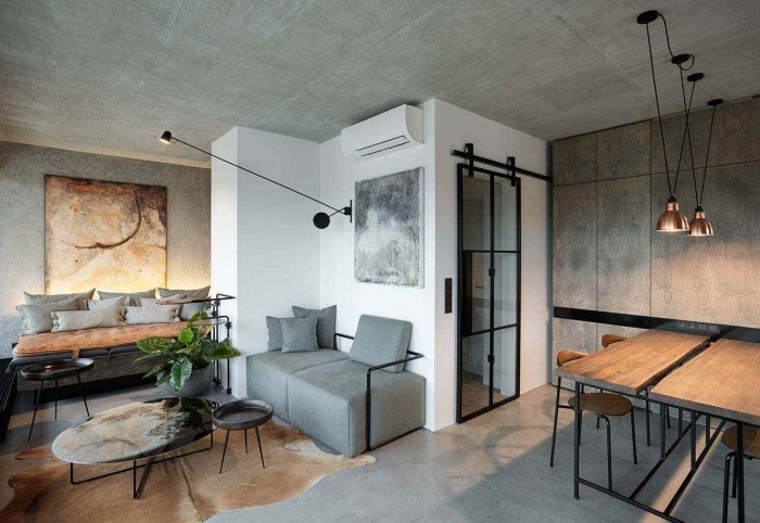 idee deco salon, canapé avec coussins en gris et table basse noire, salon à design industriel loft avec lampes suspendues en noir et cuivre