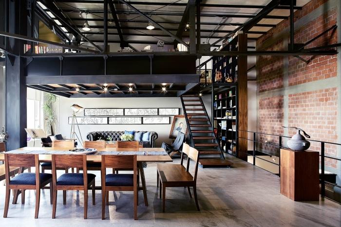 loft industriel, salle à manger ouverte vers le salon avec table à manger et chaises en bois foncé et siège bleu foncé