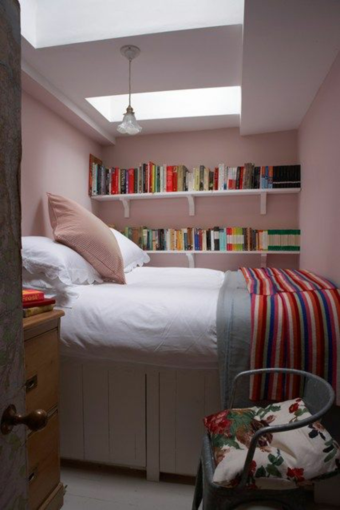 décoration chambre adulte avec un grand lit dans une niche, avec table de chevet avec 3 tiroirs profonds, chaise métallique en gris clair, étagères blanches au mur rose pastel
