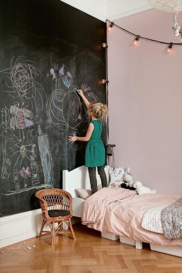 décoration chambre adulte avec tableau noir sur un mur entier pour dessiner et pour écrire, décoration murale avec des guirlandes lumineuses en forme d'ampoules , lit bas en couleur blanche, avec petit fauteuil en canne tressée à côté du lit