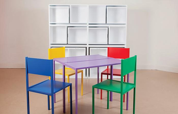 décoration chambre adulte avec quatre chaises et une table qui s'insèrent en un meuble, style ludique, chaises en jaune, vert, bleu et rouge, parquet beige artificiel