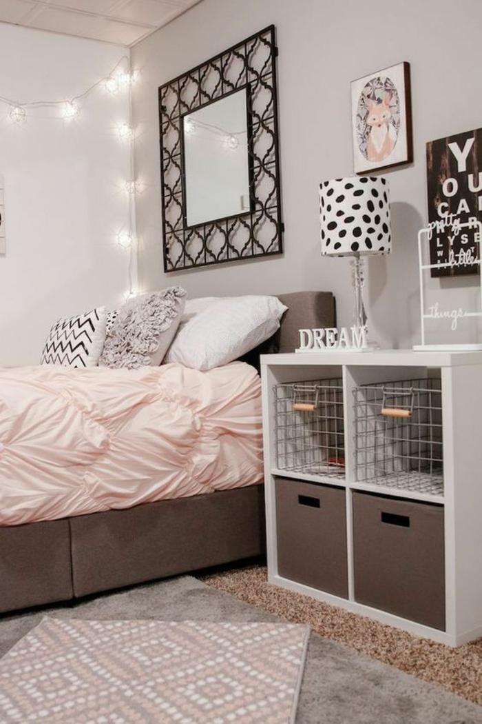 décoration chambre adulte grand lit avec couverture rose et miroir en fer forgé en forme carrée, meuble blanc bas avec des cases de rangement en métal