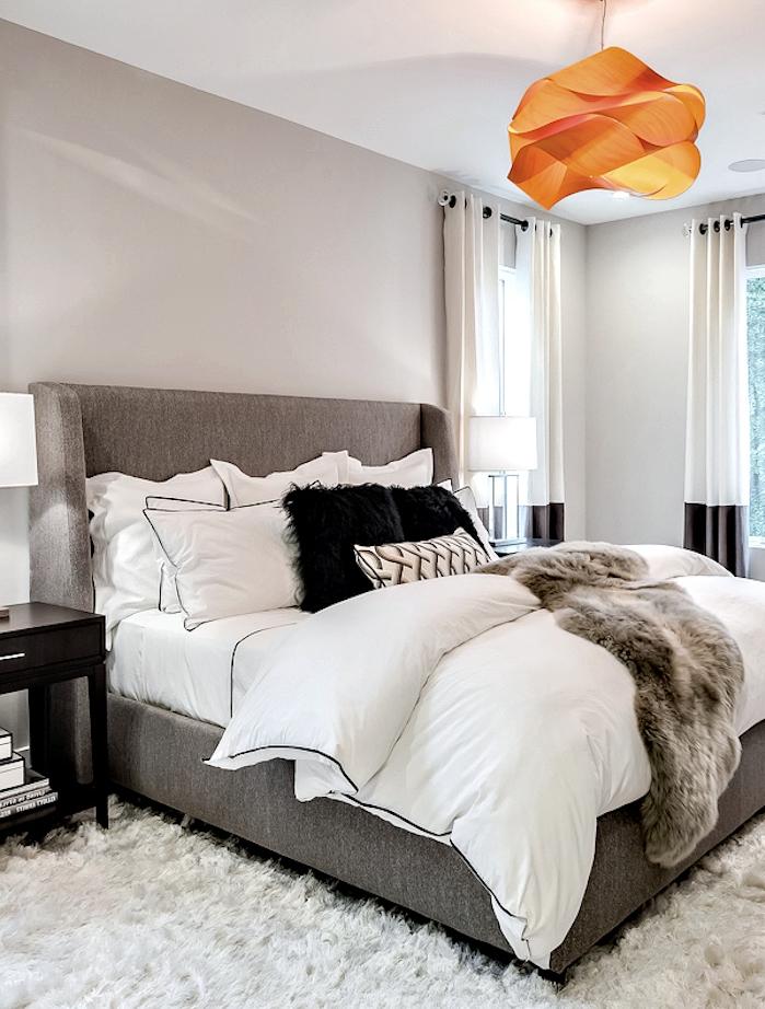 exemple de chambre gris et blanc, rafraichie par un accent orange, suspension design origami, tapis moelleux, lit gris, couvert de linge blanc