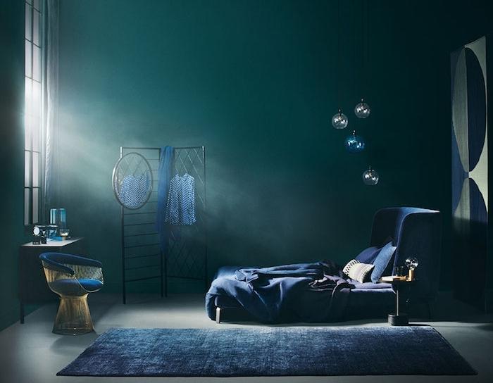 idée de chambre a coucher en bleu petrole et bleu marine, rangement grillage noir, lit et tapis bleu marine, sol gris, fauteuil design, deçor dramatique
