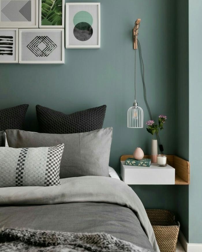 murs couleur vert de gris foncé dans une chambre adulte design, linge de lit gris et noir, table de nuit en bois, fixée au mur, mur de cadres décoratifs en tête de lit