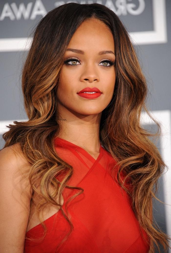 couleur chatain foncé, Rihanna en robe rouge avec col asymétrique, maquillage aux lèvres rouge et eye-liner noir