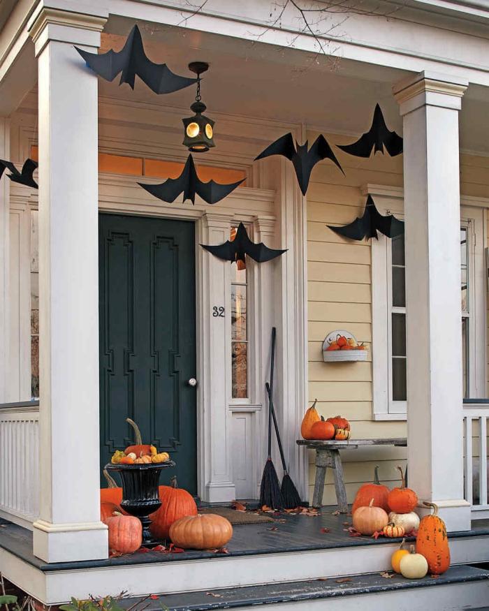 déco halloween de la véranda, façade maison beige et blanc avec porte vert foncé, déco avec citrouilles oranges et chauves-souris en papier noir
