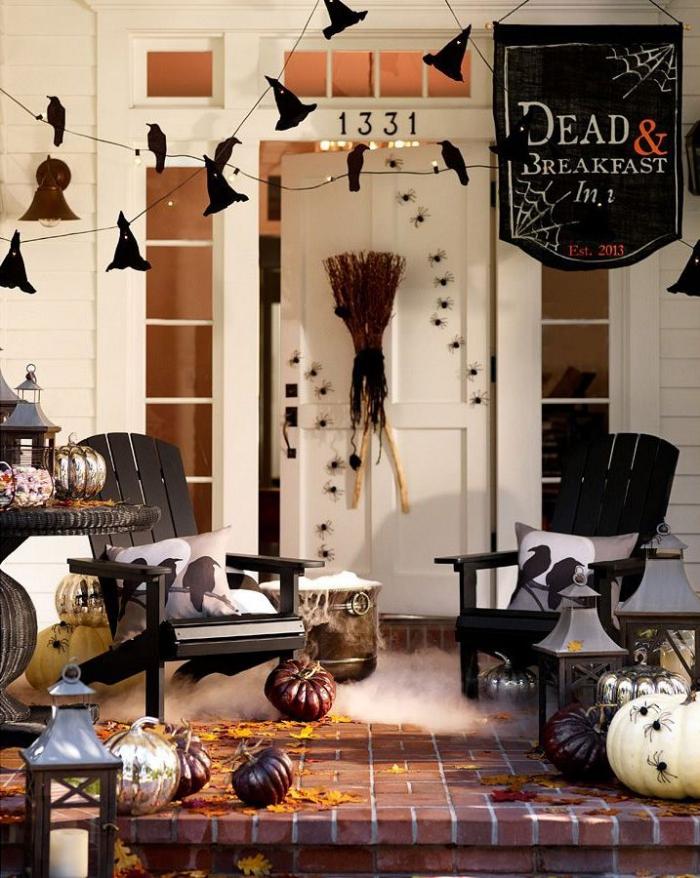 idée comment décorer sa porte d'entrée pour Halloween, façade maison blanche avec petites fenêtres et guirlande noire diy