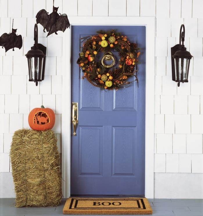 porte d'entrée bleu foncé avec déco halloween en guirlande de fleurs et fruits séchées, lanternes et chauves-souris noirs