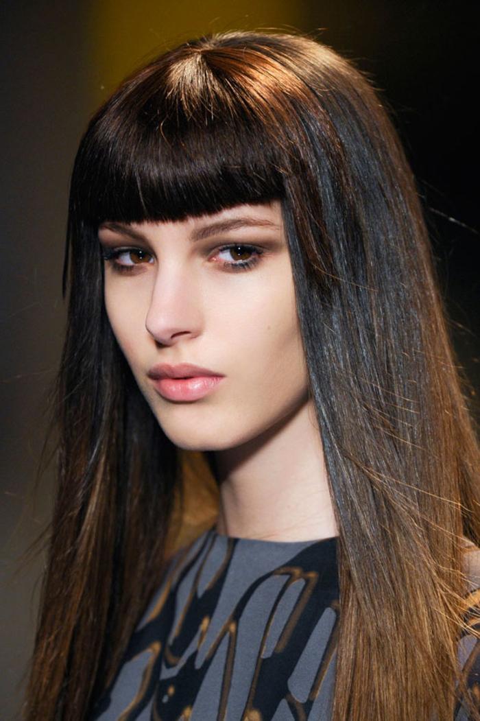 coiffure élégante à allure rétro chic avec frange droite épaisse, mettant accent sur le maquillage à effet naturel