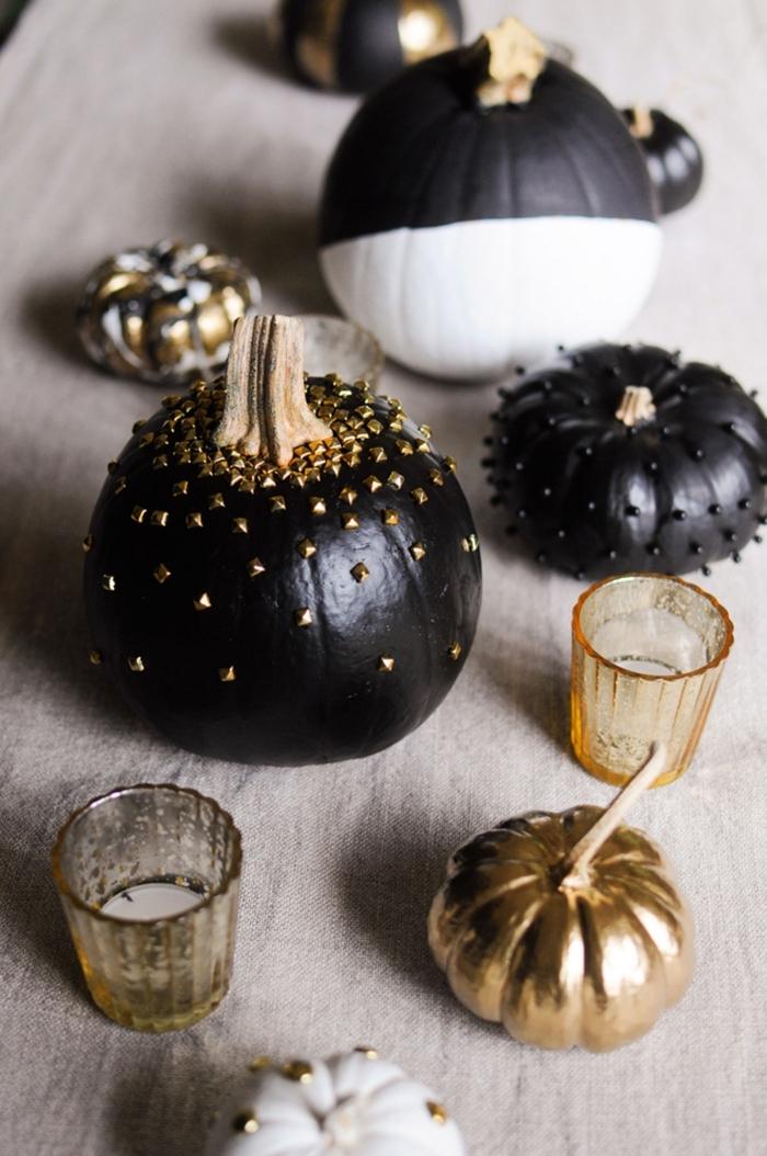 modele citrouille halloween, décoration simple avec récipient en verre et bougies blanches, petite citrouille noire avec perles noires