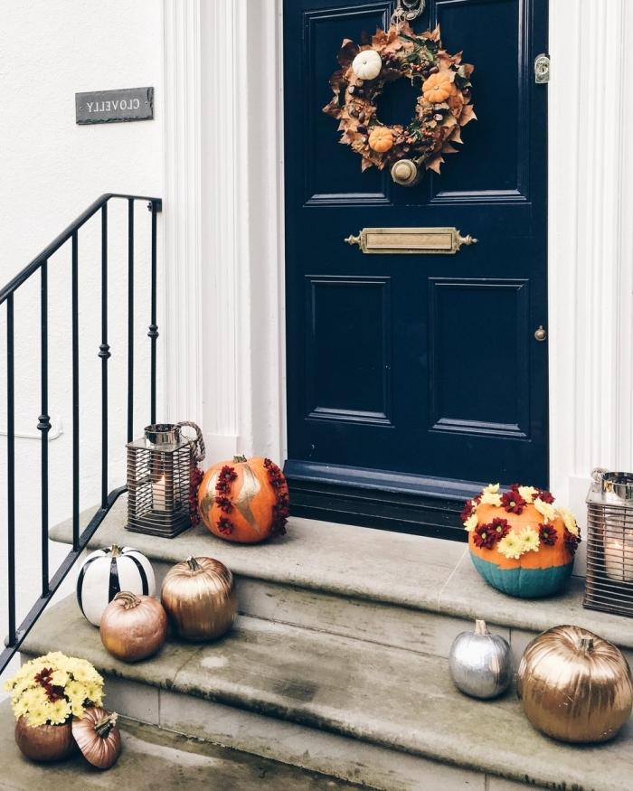 porte d'entrée bleu foncé et façade de maison blanche, guirlande en fruits et feuilles séchées pour Halloween